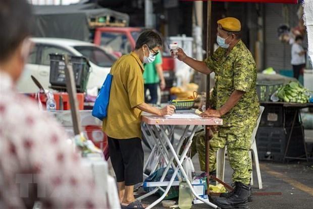 Kiểm tra thân nhiệt phòng dịch COVID-19 tại một khu chợ ở Kuala Lumpur, Malaysia, ngày 7/5/2021. (Ảnh: THX/TTXVN)