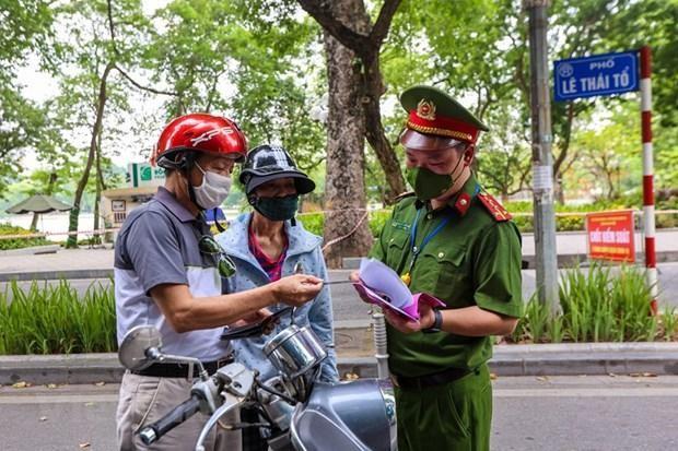 Lực lượng chức năng nhắc nhở người dân thực hiện nghiêm công tác phòng, chống dịch. (Ảnh: Minh Sơn/Vietnam+).