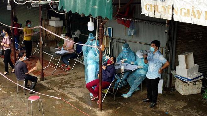 Lực lượng chức năng lấy mẫu xét nghiệm cho các tiểu thương tại chợ Phùng Khoang (Ảnh: Lê Thắng).