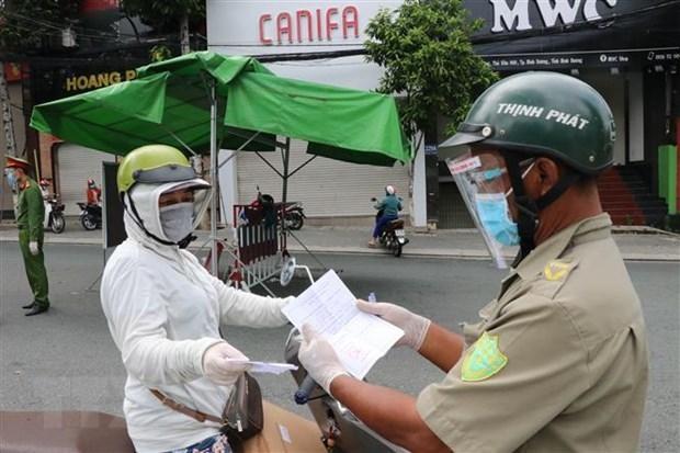Một người phụ nữ đi chợ trình giấy có giấy tiêm đủ vaccine cho lực lượng kiểm tra trên đường Yersin, thành phố Thủ Dầu Một. (Ảnh: Chí Tưởng/TTXVN).