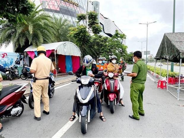 Lực lượng Công an tại chốt kiểm trên đường Phạm Văn Đồng (phường Hiệp Bình Chánh, Thủ Đức) kiểm tra giấy tờ của người lưu thông. (Ảnh: Thành Chung/TTXVN).