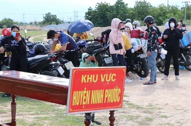 Người dân từ Đồng Nai về được tập trung theo khu vực để kiểm tra dịch bệnh trước khi đưa đi cách ly tập trung. (Ảnh: Công Thử/TTXVN).