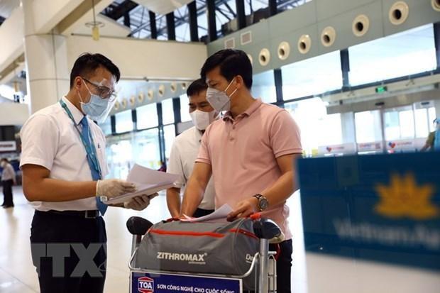 Nhân viên của Vietnam Airlines kiểm tra giấy tờ của hành khách trước khi vào làm thủ tục. (Ảnh: Huy Hùng/TTXVN).