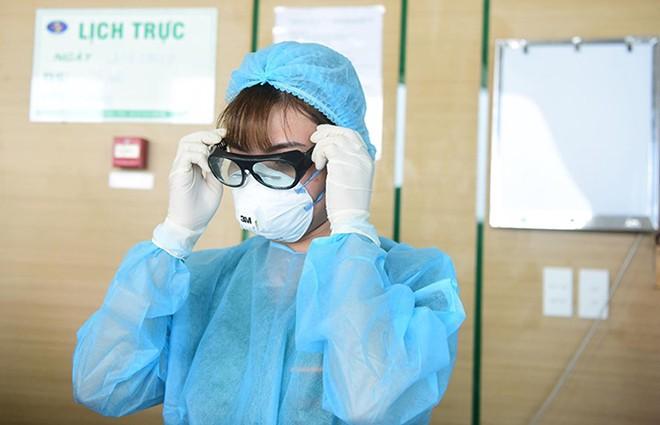 Nhân viên y tế mặc đồ bảo hộ vào khu vực cách ly bệnh nhân viêm phổi tại Bệnh viện Bệnh Nhiệt đới Trung ương cơ sở 2.
