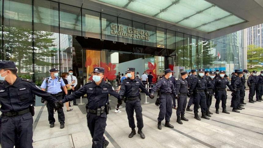 Các nhân viên an ninh tạo thành một chuỗi người khi họ bảo vệ trụ sở của Evergrande, nơi mọi người tụ tập để yêu cầu hoàn trả các khoản vay và các sản phẩm tài chính ở Thâm Quyến, Trung Quốc