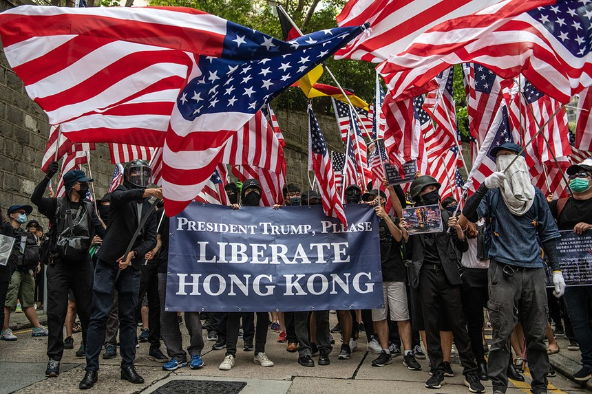 Người biểu tình vẫy cờ bên ngoài lãnh sự quán Mỹ ở Hồng Kông sau khi gửi đơnkêu cứu Tổng thống Mỹ Donald Trump. Ảnh: Getty Images.