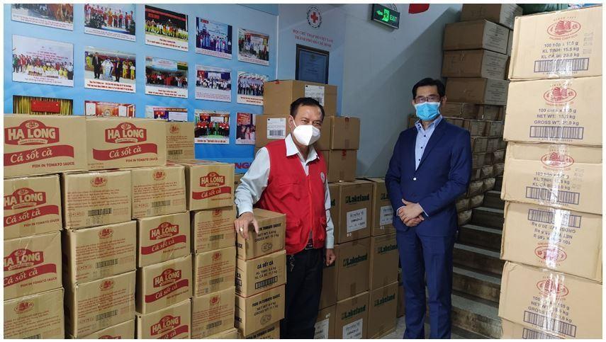 Ông Harry Loh, Tổng giám đốc Ngân hàng UOB Việt Nam (phải) và ông Trần Trường Sơn, Chủ tịch Hội Chữ thập đỏ TP.HCM (trái) cùng với số lượng đồ hộp và vật tư y tế sẵn sàng để phân phối
