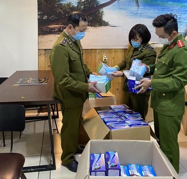 Đội Quản lý thị trường số 15 phối hợp với công an quận Hoàng Mai kiểm tra khẩu trang thu giữ. (Ảnh: Đức Duy/Vietnam+)