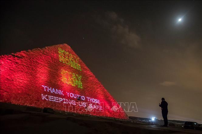 """Đại Kim tự tháp được thắp sáng thông điệp """"Hãy ở nhà"""", tại Cairo, Ai Cập, tối 30/3/2020. Ảnh: AFP/TTXVN"""