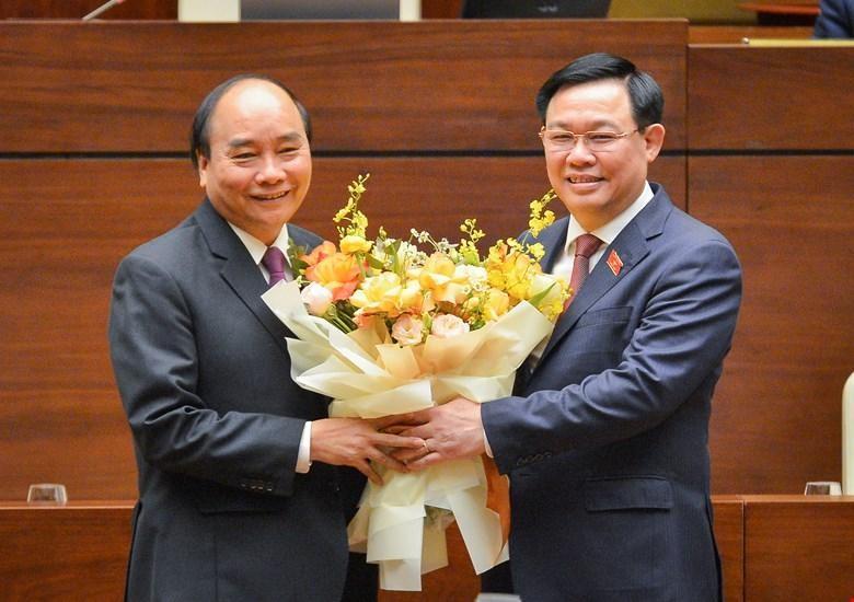 Thủ tướng Nguyễn Xuân Phúc (trái) nhận hoa chúc mừng của Chủ tịch Quốc hội Vương Đình Huệ (Ảnh Quochoi.vn).