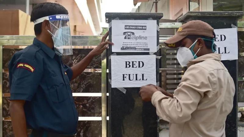 Nhân viên an ninh tại một bệnh viện tư nhân ở thành phố Allahabad, Ấn Độ thông báo hôm 22/4 tới người dân rằng bệnh viện này đã hết giường. Ảnh: AFP