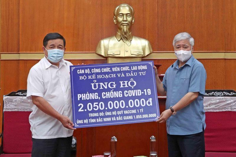 Đại diện Bộ Kế hoạch và Đầu tư, Bộ trưởng Nguyễn Chí Dũng (bìa trái) trao 2,05 tỷ đồng đóng góp cho hoạt động phòng chống dịch Covid-19 cho Chủ tịch Ủy ban Trung ương MTTQ Việt Nam Đỗ Văn Chiến (Ảnh: Đức Trung)