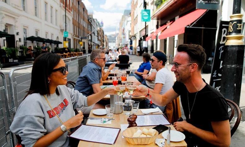Thực khách thưởng thức đồ uống tại một nhà hàng ở London, hưởng ứng chương trình kích cầu EOHO của chính phủ Anh. Ảnh: AFP
