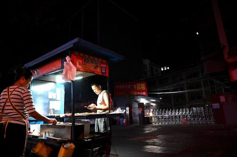 Một người bán đồ ăn trước lối vào một khu công nghiệp ở thành phố Đông Quan, tỉnh Quảng Đông, Trung Quốc - nơi bị ảnh hưởng bởi thiếu điện. Ảnh: AFP